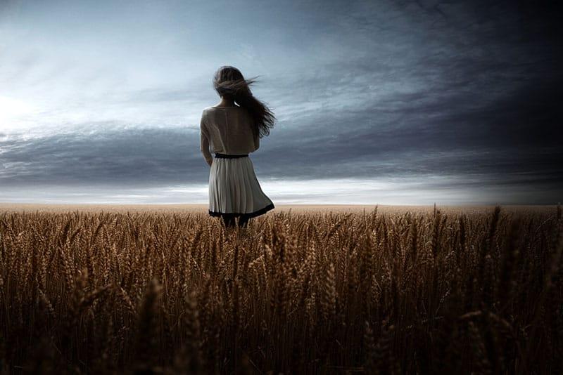 junge blonde Frau, die in der Mitte des Feldes still steht