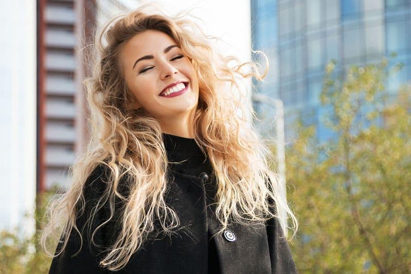 junge blonde Frau, die draußen lächelt