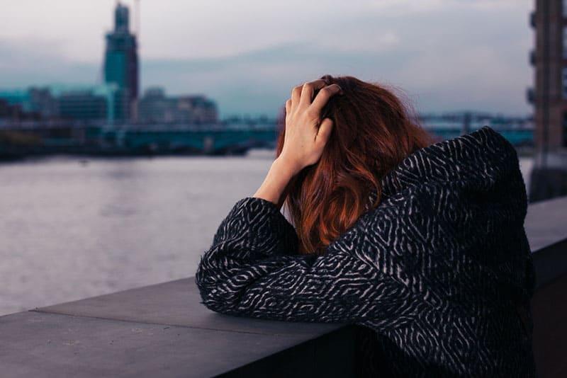junge rothaarige Frau, die sich an die Wand am Fluss in der Stadt lehnt