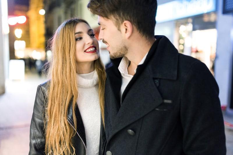 schöne Blondine mit weißer Mütze geht mit Freund