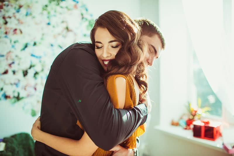 schöne junge Paare umarmen sich in ihrem Schlafzimmer