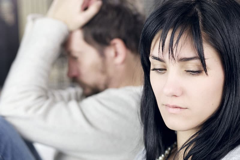 traurige Frau mit Mann auf dem Bett