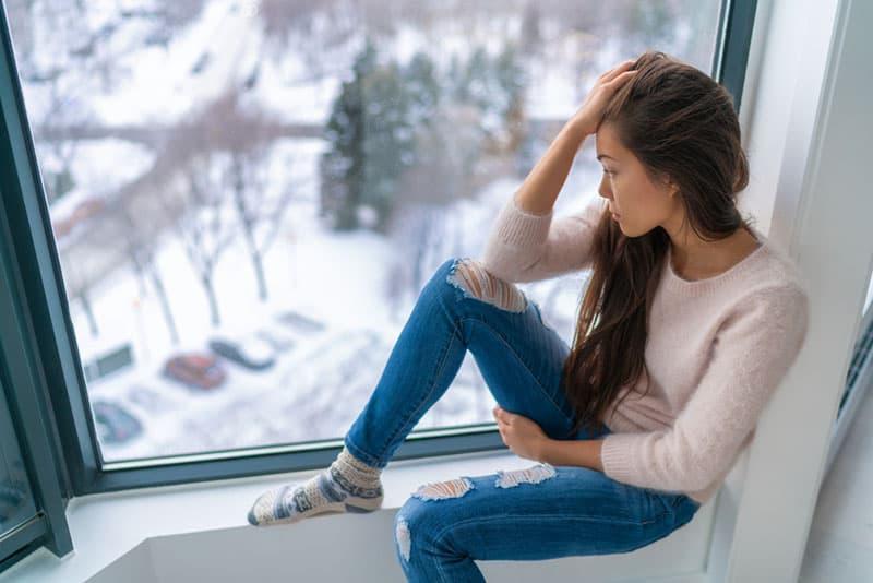 traurige junge Frau, die am Fenster sitzt und denkt