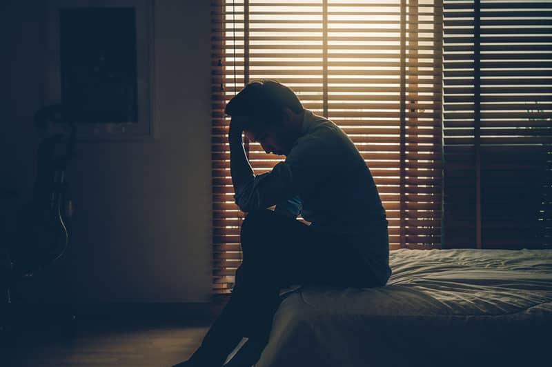 trauriger Geschäftsmann, der auf dem Bett mit seinen Händen auf seinem Kopf sitzt