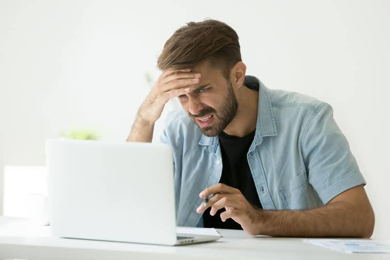 überraschter Mann bei der Arbeit am Laptop