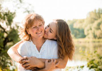 Eine erwachsene Frau umarmt ihre Tochter im Teenageralter