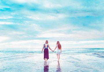 zwei Freundinnen, die am Strand spazieren gehen