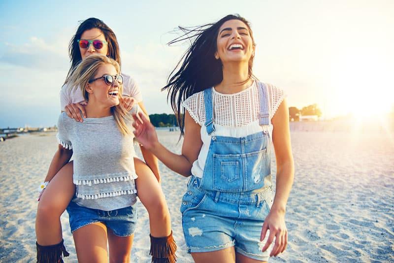 Freundinnen am Strand spazieren gehen und lachen
