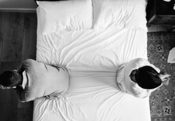 Bild von der Decke eines Paares, das im Schlafzimmer mit dem Rücken zueinander sitzt