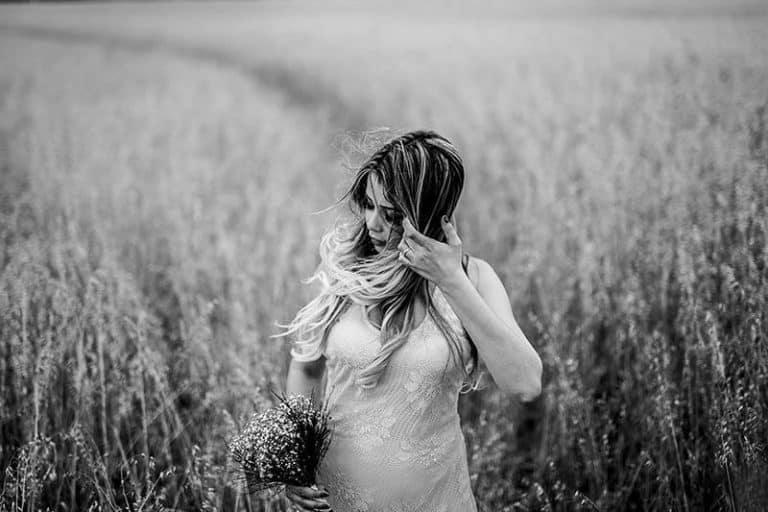 Ein Mädchen in einem weißen Kleid geht über das Feld