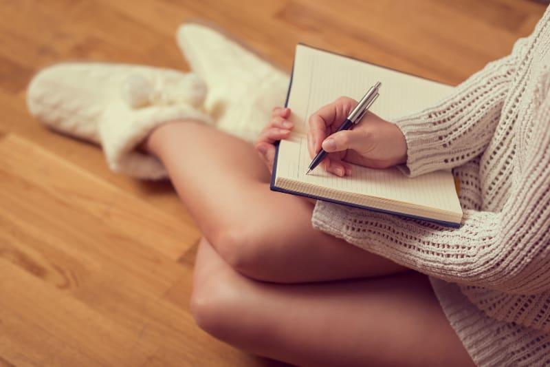 Das Mädchen sitzt auf dem Boden am Kamin und schreibt einen Brief