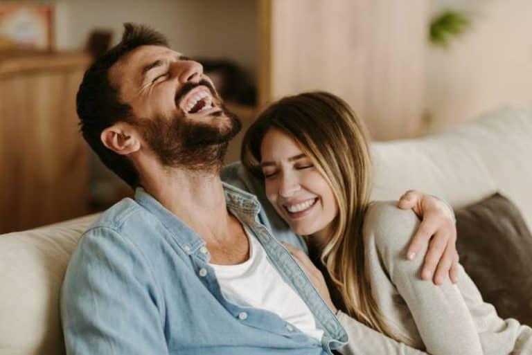 Das umarmende Paar genießt das Wohnzimmer