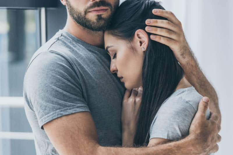 bärtiger Mann, der junge traurige Frau umarmt und unterstützt
