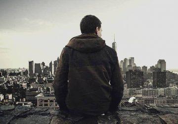 Der Mann in der Jacke steht auf und beobachtet die Stadt