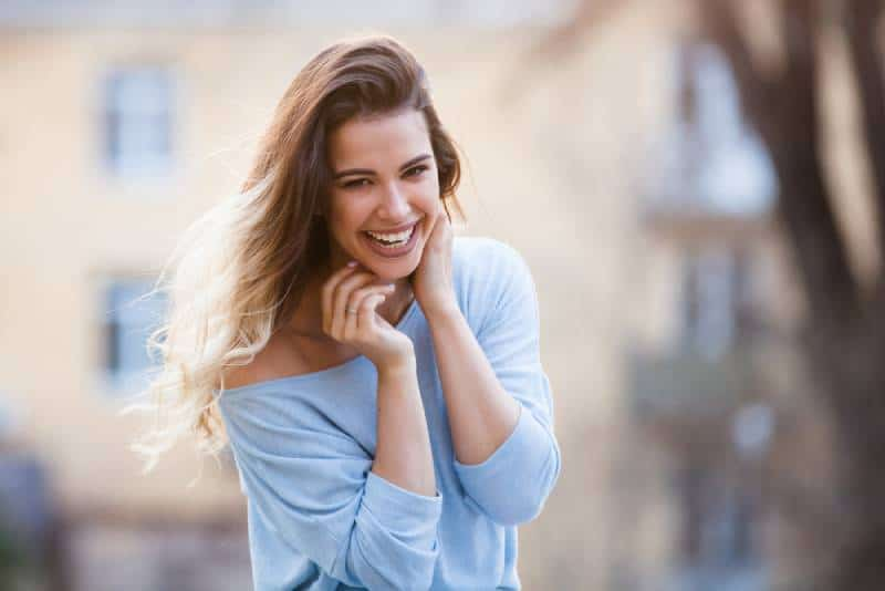glückliche Frau, die draußen auf Wind lächelt