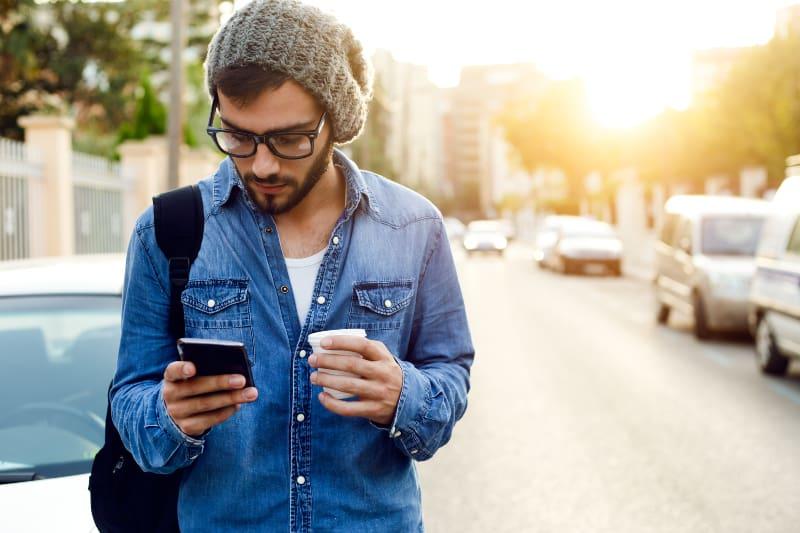 Ein junger Mann hält einen Kaffee in der Hand und tippt eine Nachricht auf sein Handy