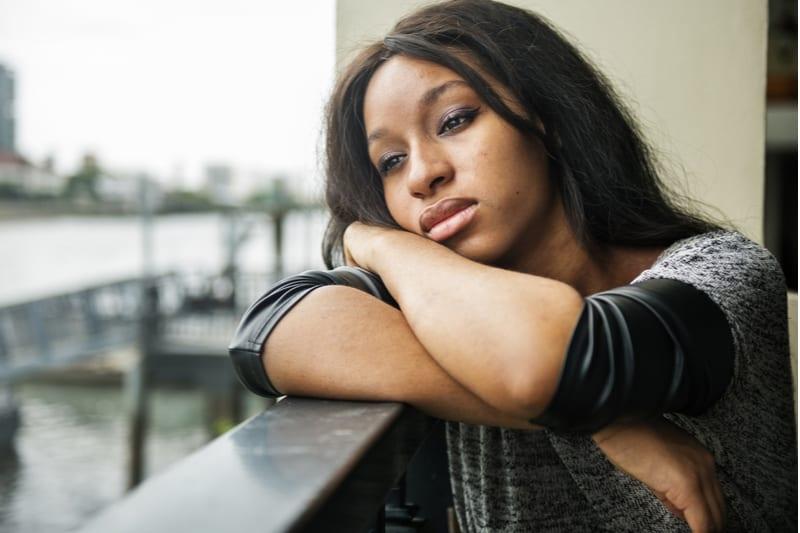 Eine depressive schwarze Frau sitzt auf dem Balkon