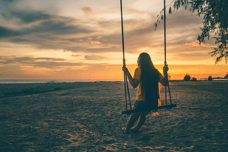 Frau am Strand draußen bei Sonnenuntergang