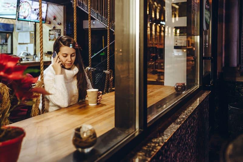 Frau am Telefon trinkt Tee