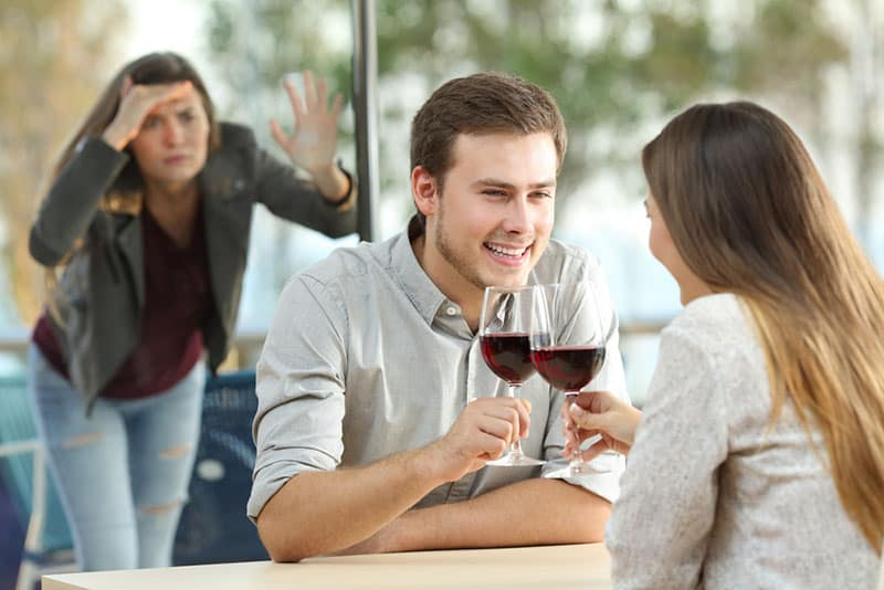 Frau, die Paar am Tisch ansieht