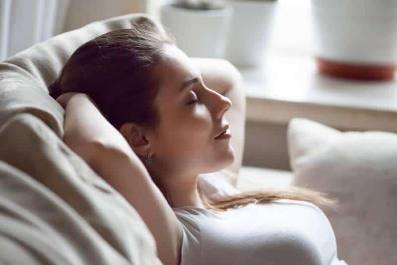 Frau entspannt sich auf ihrem Sofa