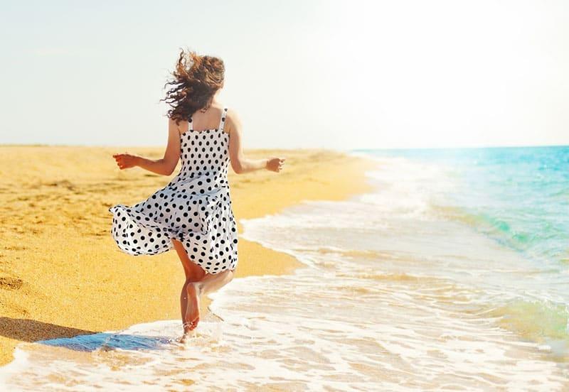 Frau im Kleid, die am Strand durch Meer geht