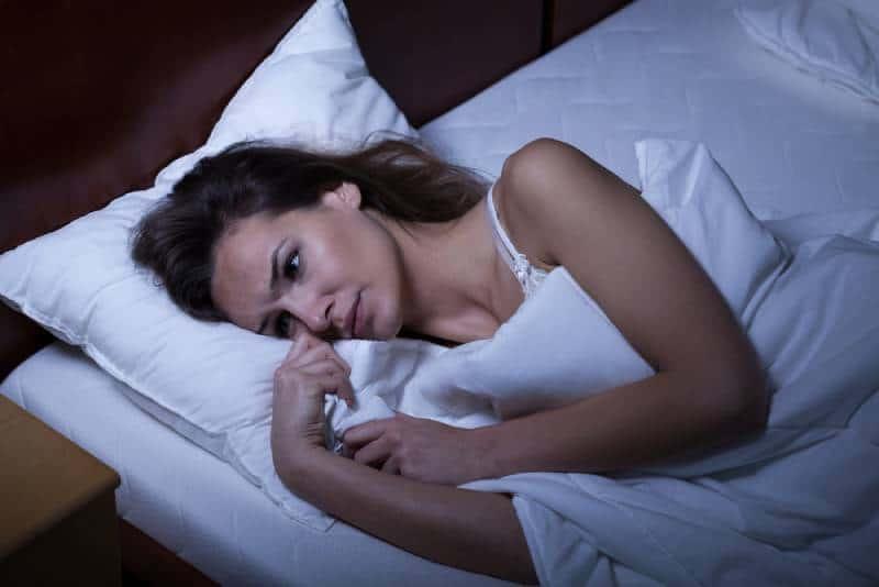 Frau liegt auf dem Bett und kann nicht schlafen
