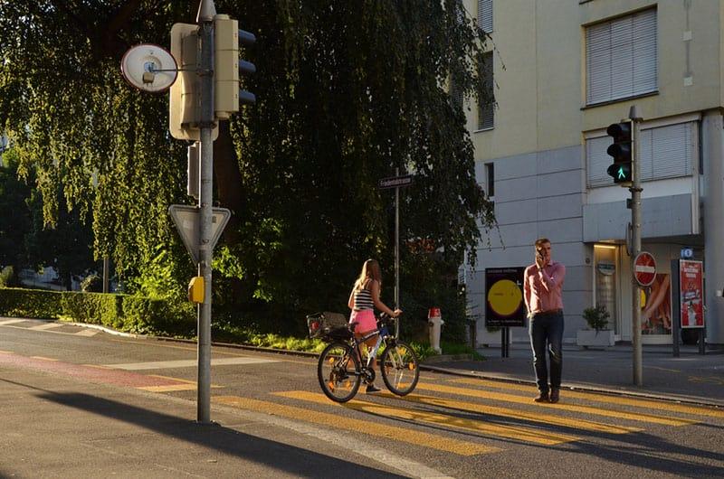 Frau mit Fahrrad überquert die Straße
