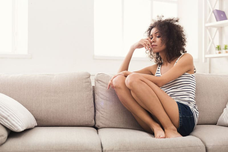 Frau mit lockigem Haar sitzt auf dem Sofa