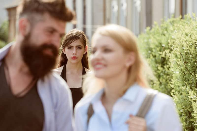 Frau schaut Paar traurig an