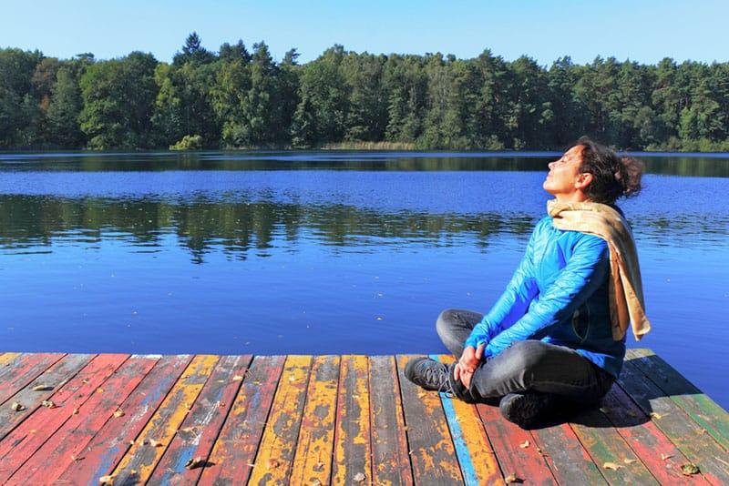 Frau sitzt und genießt am See