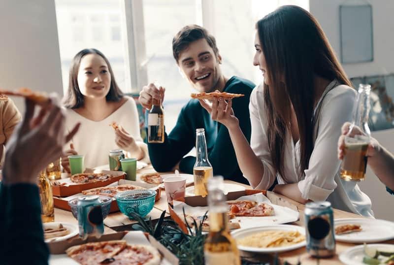 Freunde essen Pizza und reden Witze