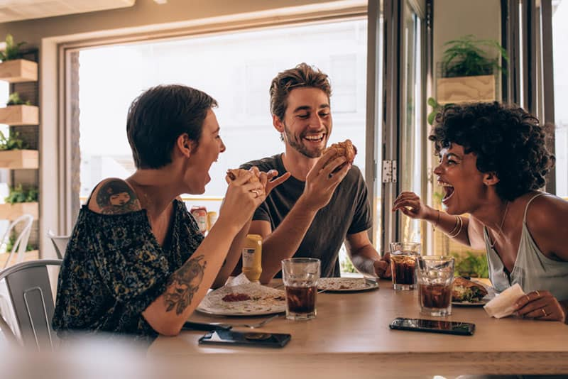 Freunde essen und lachen zusammen