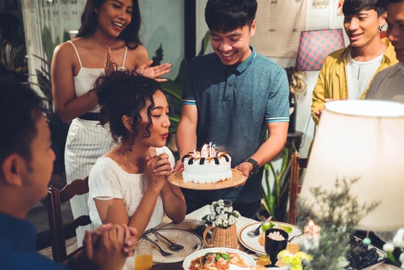 Freunde feiern Geburtstag eines Freundes mit Kuchen