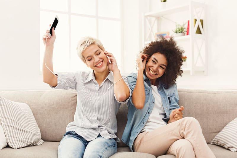 Freunde hören gemeinsam Musik auf der Couch