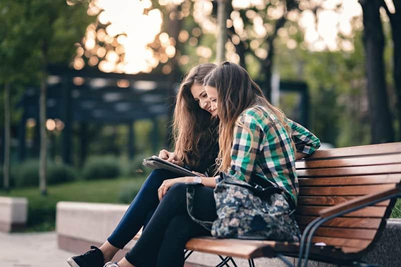 Freunde sitzen auf dem Stuhl im Park