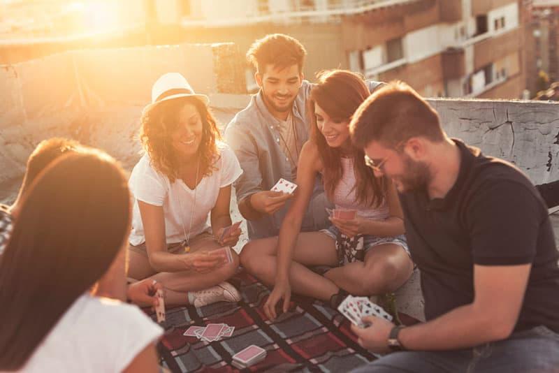 Freunde spielen Karten auf dem Dach