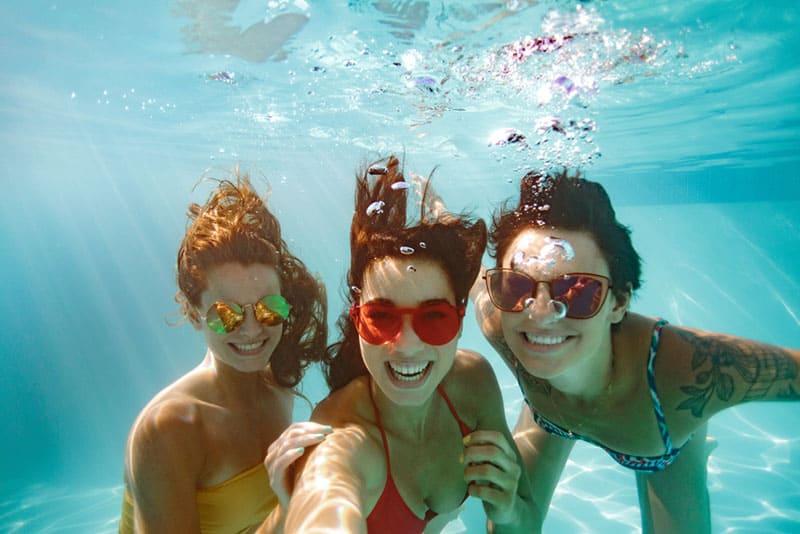 Freunde tauchen im Pool und machen ein Selfie