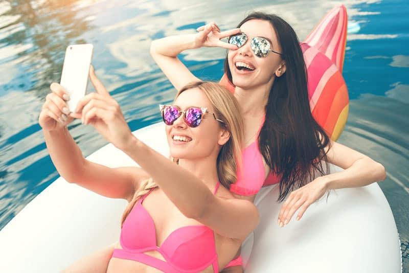 Freundinnen auf Einhorn im Pool bekommen ein Bild