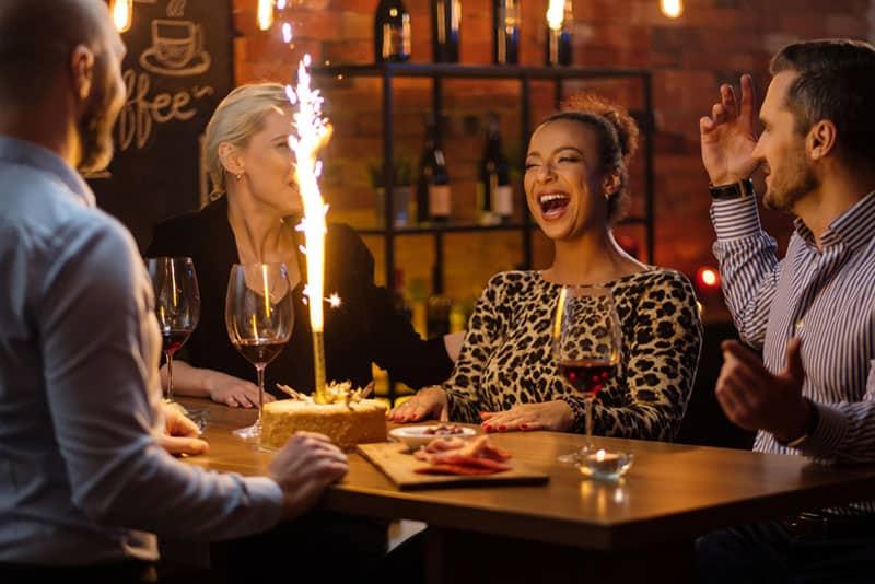 Geburtstagskind lächelt mit ihren Freunden am Tisch