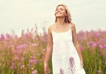 glückliche blonde Frau im Blumenfeld