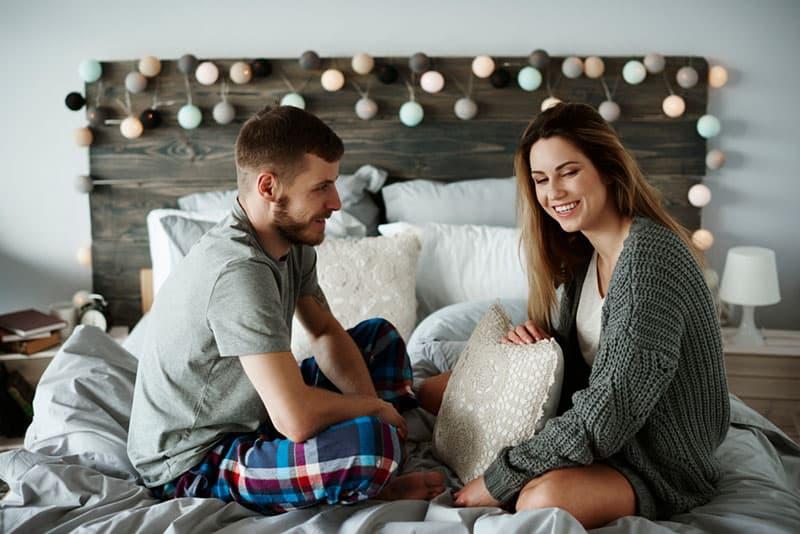 Junge und Mädchen sitzen auf dem Bett und reden