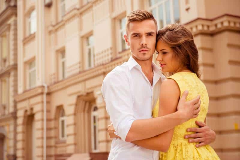 Junger Mann beschützt seine Freundin und umarmt
