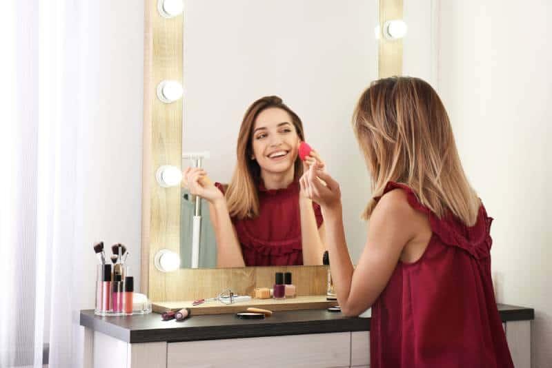 Lächelnde Frau, die sich vor dem Spiegel schminkt