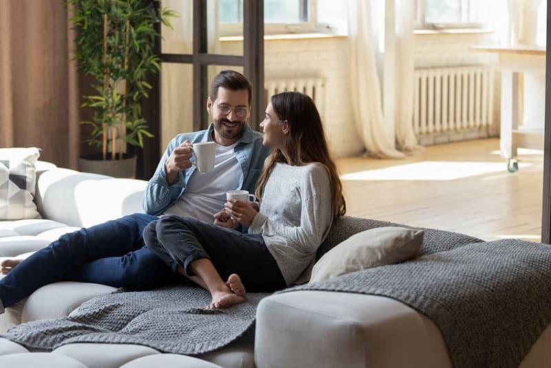 Liebespaar auf der Couch trinkt Kaffee