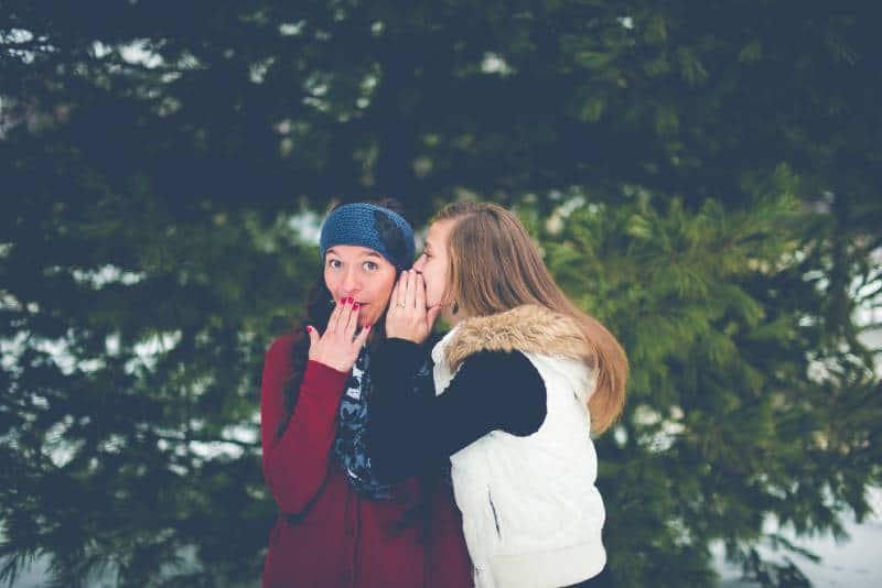 Mädchen, das ihrer Freundin ein Geheimnis erzählt