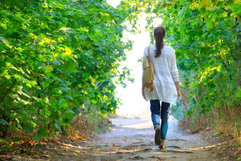 Mädchen geht den Weg im Wald entlang