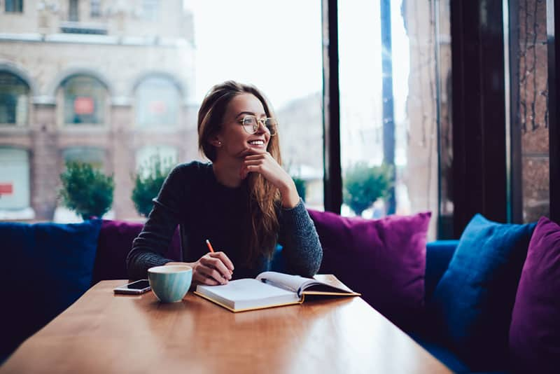 Mädchen mit Brille, die im Café schreibt