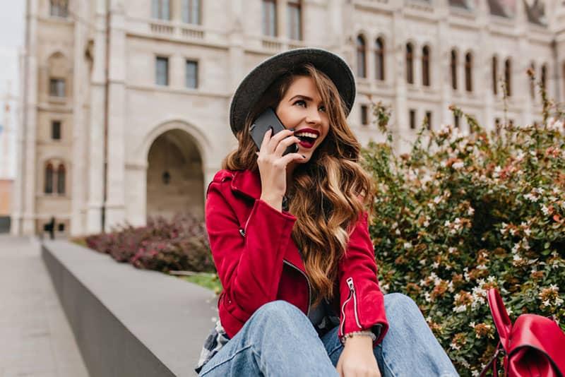 Mädchen mit Hut und roter Jacke am Telefon sprechen