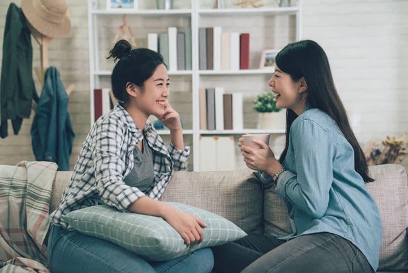 Mädchen reden auf der Couch und lächeln